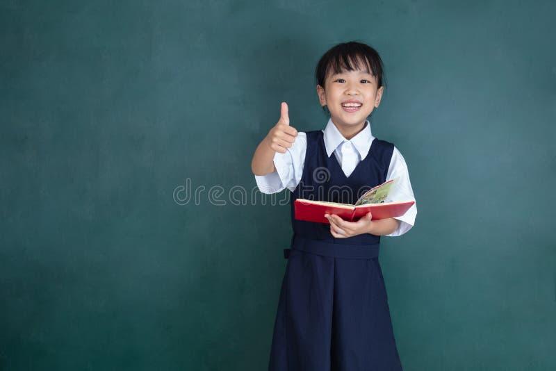 Menina chinesa asiática no uniforme que mostra os polegares acima contra g imagem de stock royalty free
