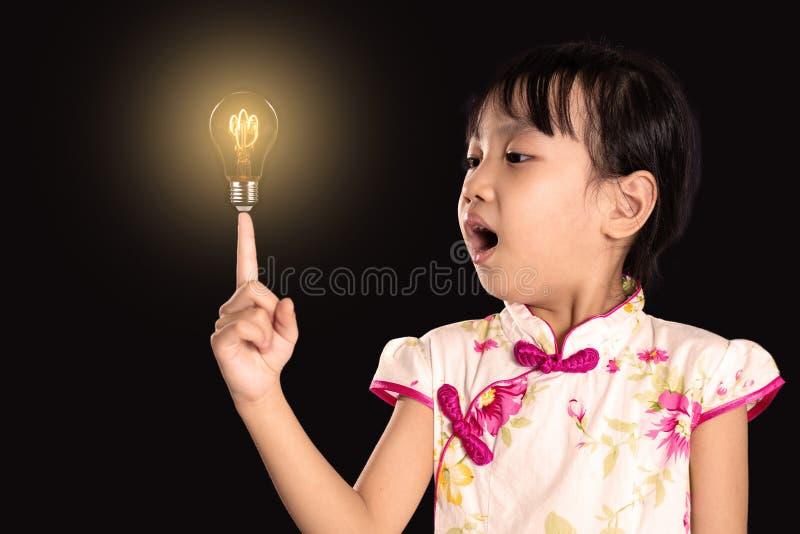 Menina chinesa asiática que aponta o dedo até a ampola imagem de stock