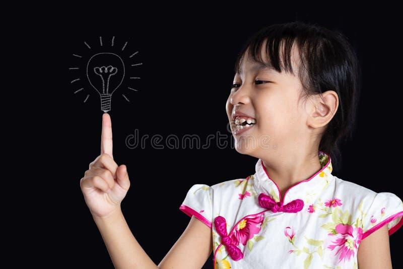 Menina chinesa asiática que aponta o dedo até o bulbo imagens de stock royalty free