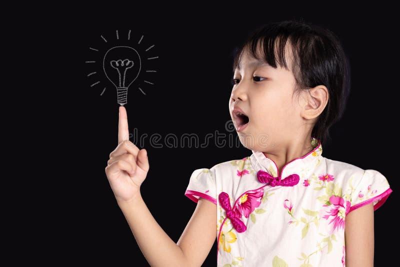 Menina chinesa asiática que aponta o dedo até o bulbo fotografia de stock