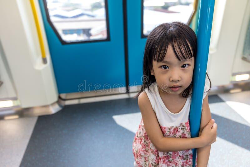 Menina chinesa asiática que está dentro de um trânsito do MRT foto de stock royalty free