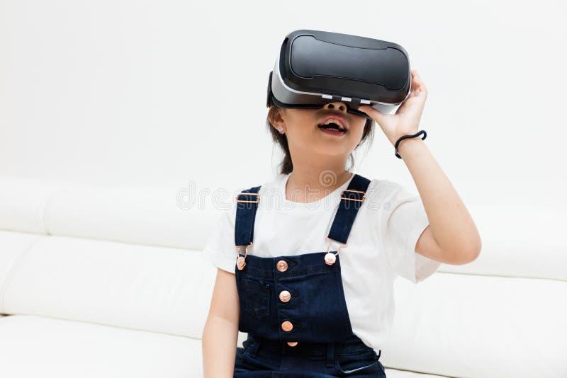 Menina chinesa asiática que experimenta a realidade virtual em casa imagens de stock