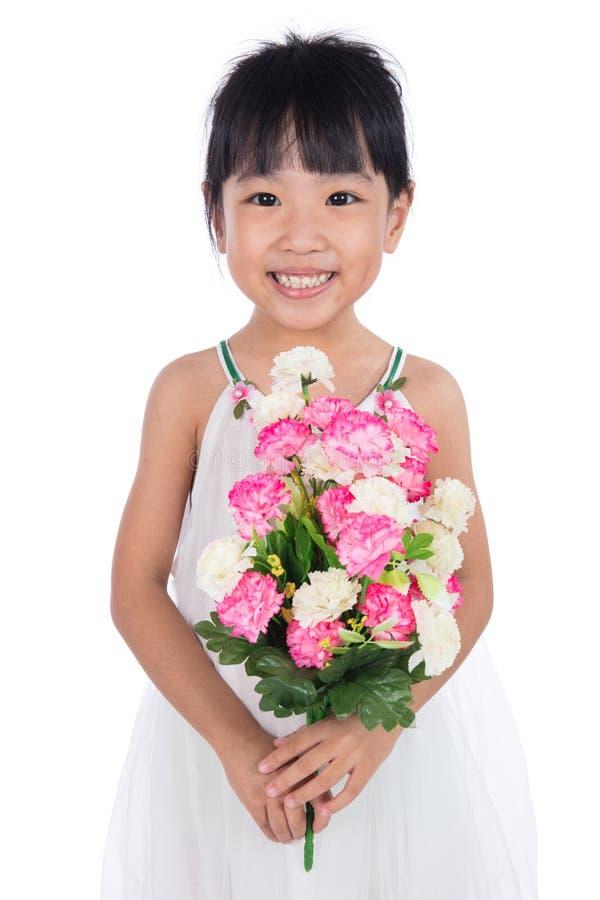 Menina chinesa asiática que guarda as flores que cumprimentam para o ` s da mãe fotografia de stock