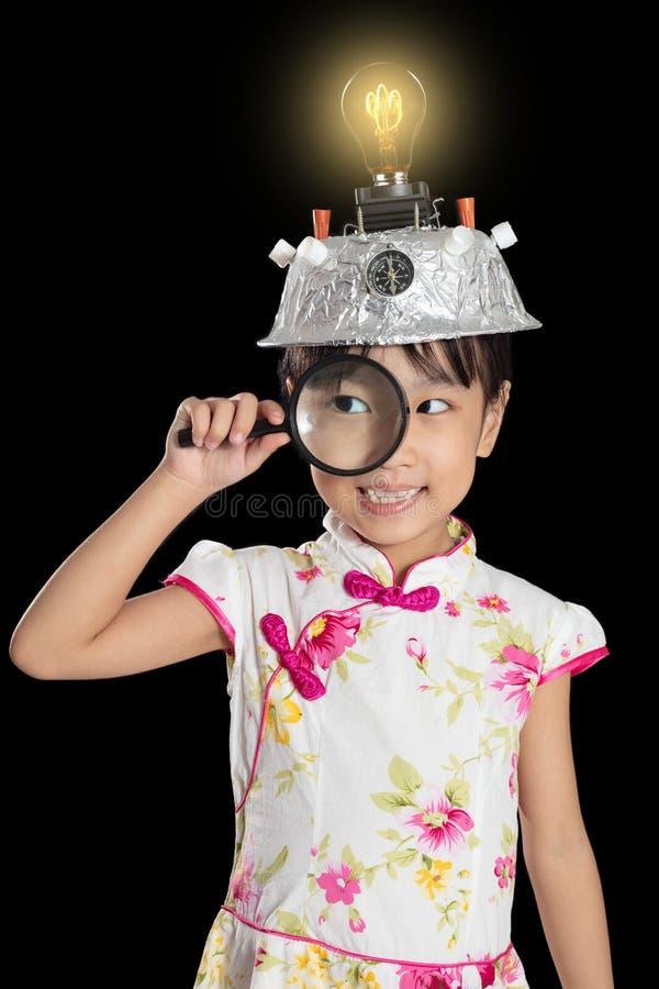 Menina chinesa asiática que guarda a lente de aumento com realidade virtual fotografia de stock royalty free