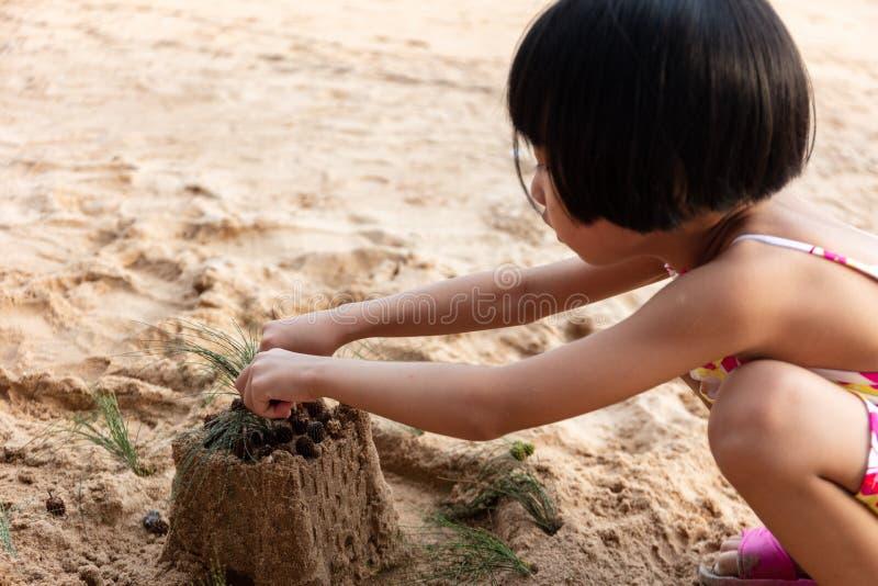 Menina chinesa asiática que joga a areia na praia fotos de stock