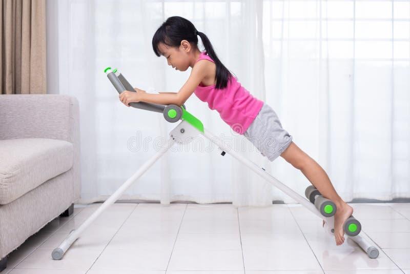 Menina chinesa asiática que joga a máquina do exercício na vida imagem de stock royalty free