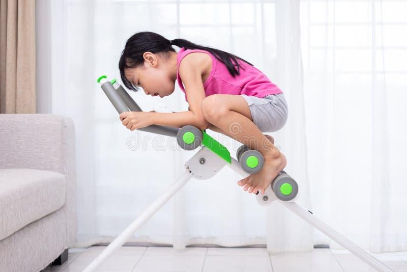 Menina chinesa asiática que joga a máquina do exercício na vida fotos de stock