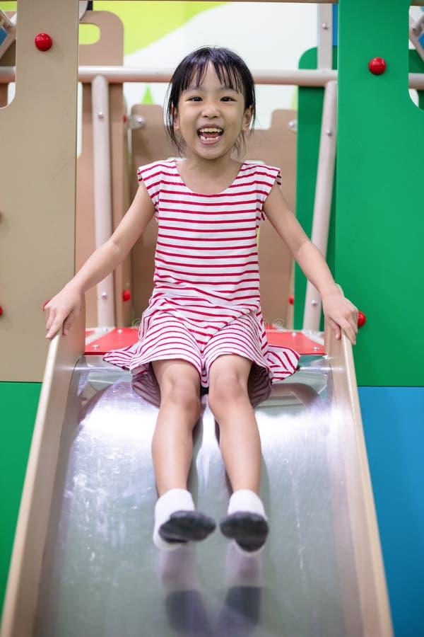 Menina chinesa asiática que joga na corrediça fotografia de stock royalty free