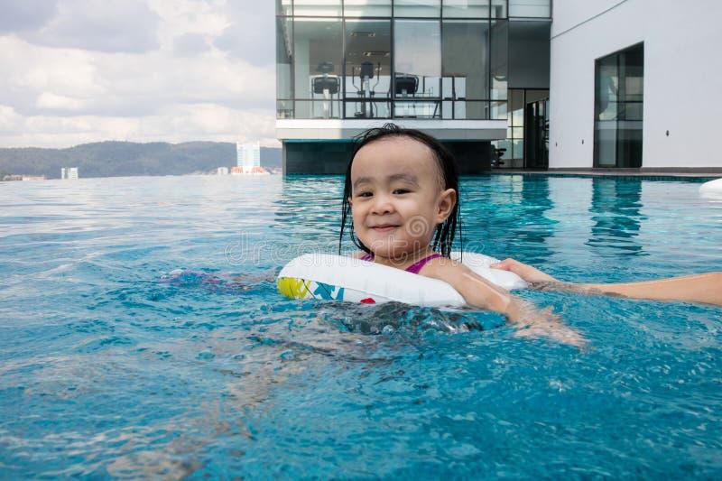 Menina chinesa asiática que joga na piscina exterior fotografia de stock royalty free