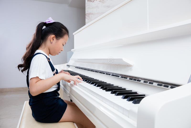 Menina chinesa asiática que joga o piano clássico em casa fotografia de stock