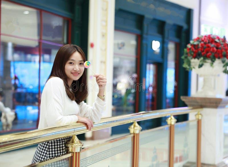 Menina chinesa asiática que lambe um pirulito fotografia de stock