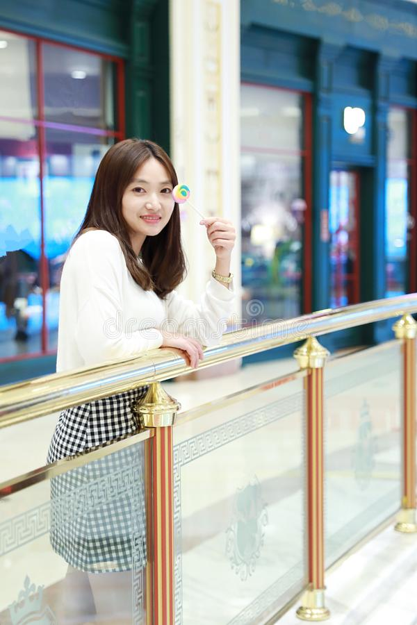 Menina chinesa asiática que lambe um pirulito fotos de stock royalty free