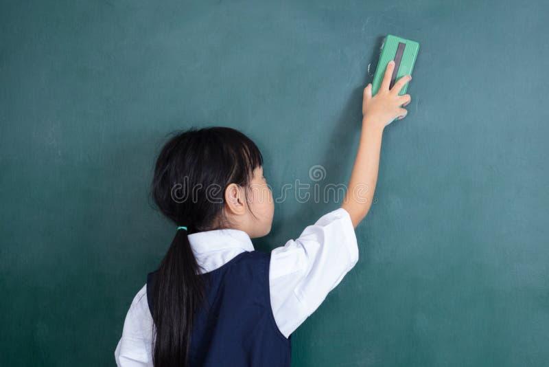Menina chinesa asiática que limpa o quadro-negro verde imagem de stock