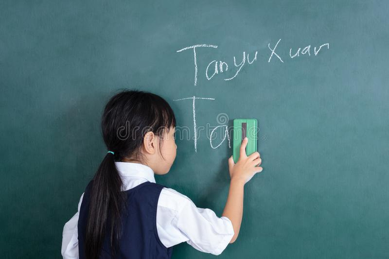 Menina chinesa asiática que limpa o quadro-negro verde foto de stock