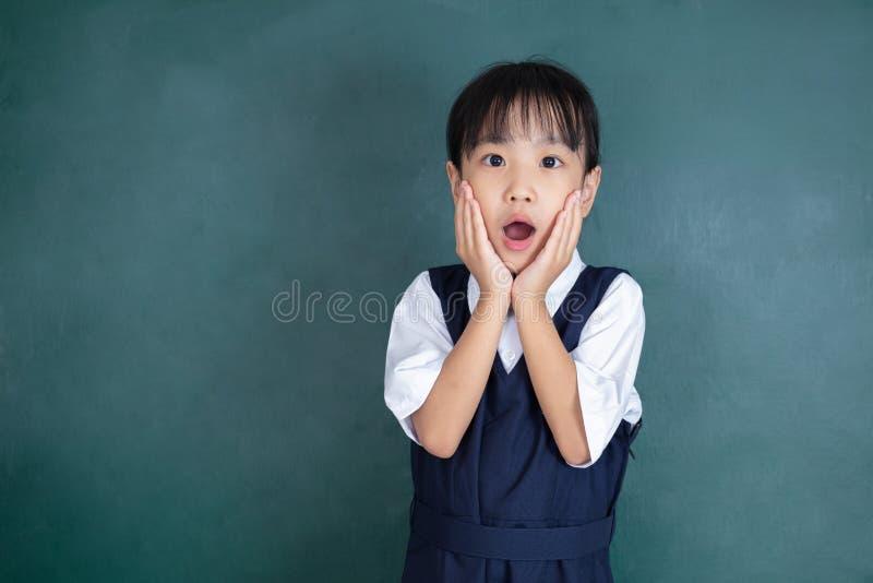 Menina chinesa asiática que mostra a expressão surpreendida com mão fotografia de stock
