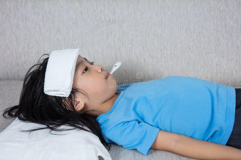 Menina chinesa asiática que obtém a medida para o temperat da febre fotografia de stock
