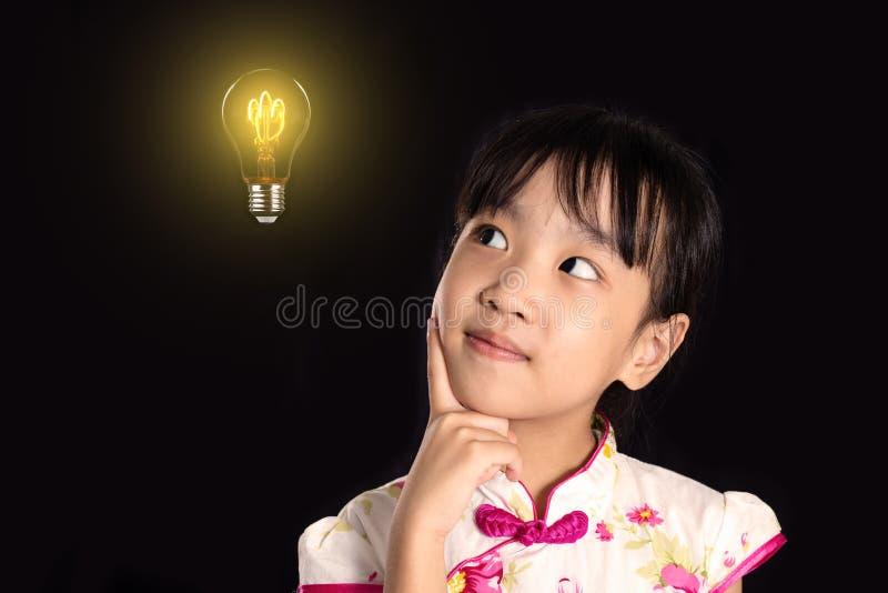 Menina chinesa asiática que pensa com ampola foto de stock royalty free