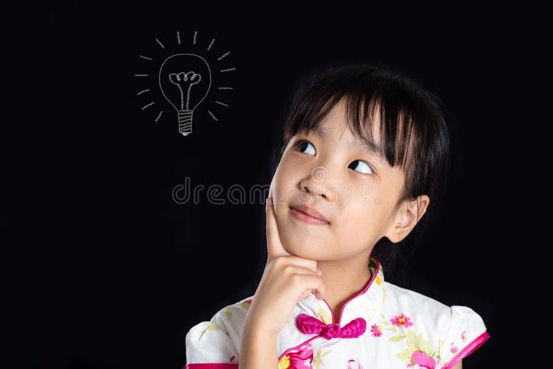 Menina chinesa asiática que pensa com esboço do bulbo fotos de stock royalty free