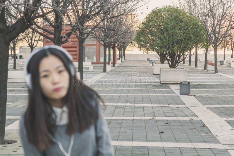 Menina chinesa bonita nova com fones de ouvido intencionalmente fora de foco imagem de stock royalty free