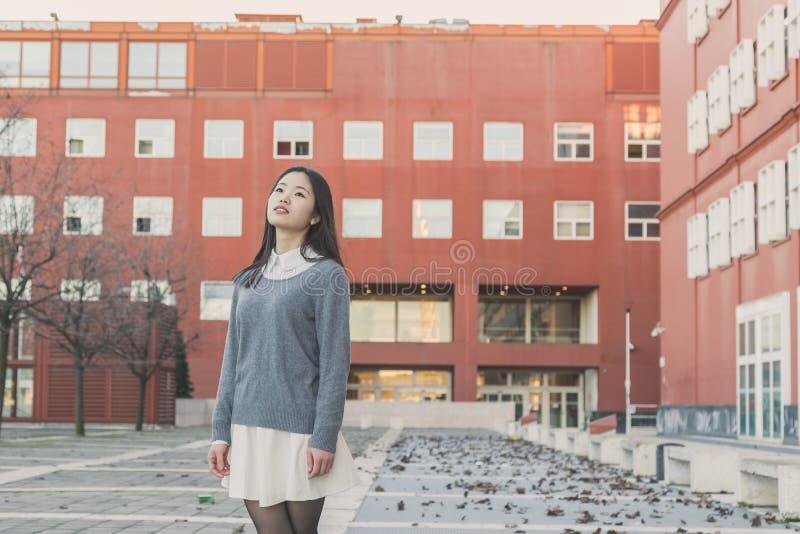 Menina chinesa bonita nova que levanta nas ruas da cidade fotografia de stock