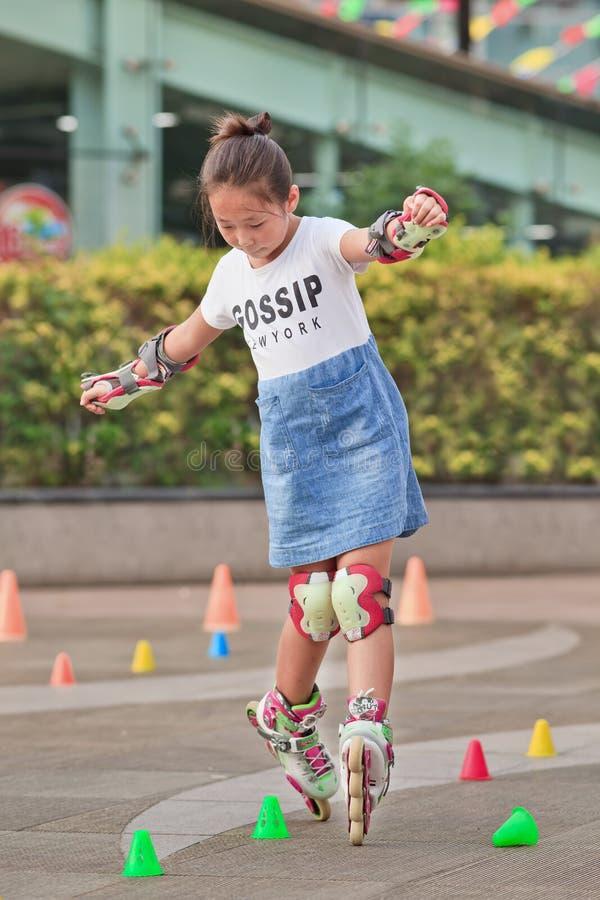 Menina chinesa bonita que pratica inline patinar, Pequim, China imagens de stock