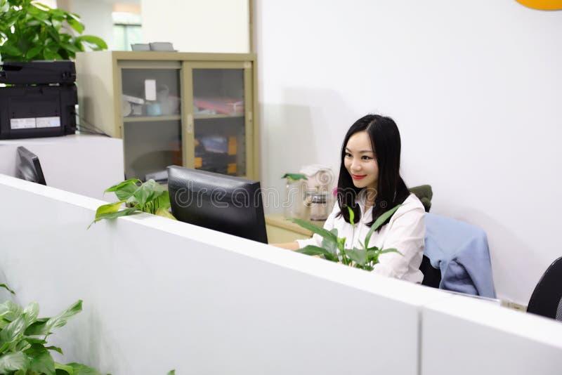 A menina chinesa da mulher da senhora do escritório de Ásia na cadeira faz uma mesa do uso da chamada telefonar ao local de traba fotografia de stock