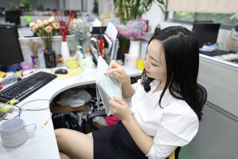 Menina chinesa da mulher da senhora do escritório de Ásia na programação do calendário da verificação da cadeira no local de trab imagem de stock