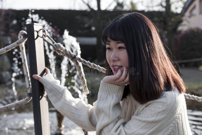 A menina chinesa nova relaxa em um parque exterior imagens de stock royalty free