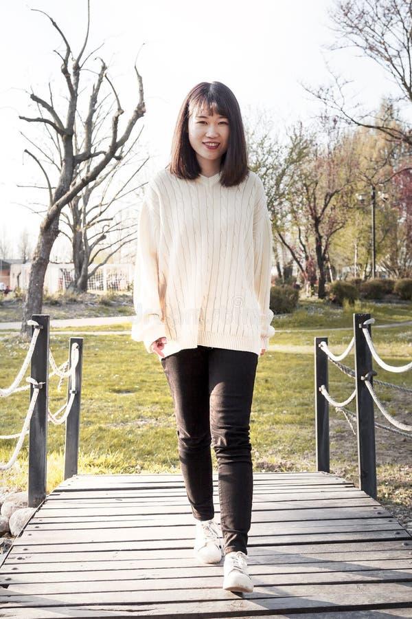A menina chinesa nova relaxa em um parque exterior imagem de stock