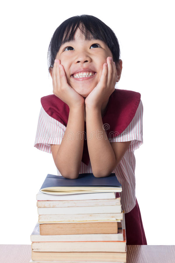Menina chinesa pequena asiática com as pilhas dos livros fotos de stock