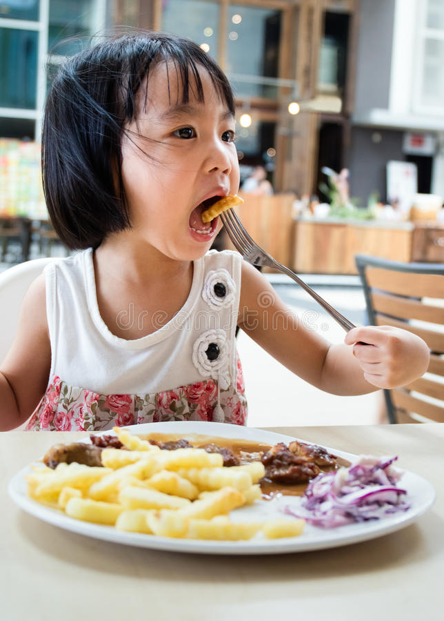 Menina chinesa pequena asiática que come o alimento ocidental fotografia de stock royalty free