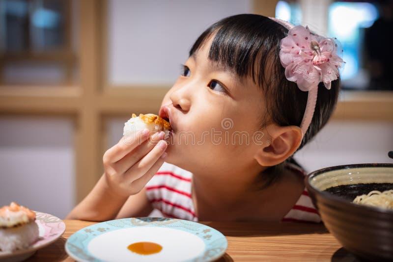 Menina chinesa pequena asiática que come o sushi fotos de stock