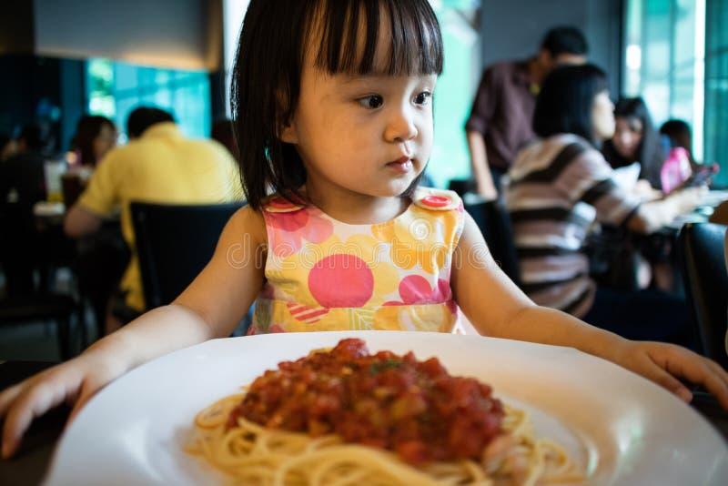 Menina chinesa pequena asiática que espera para comer os espaguetes fotos de stock