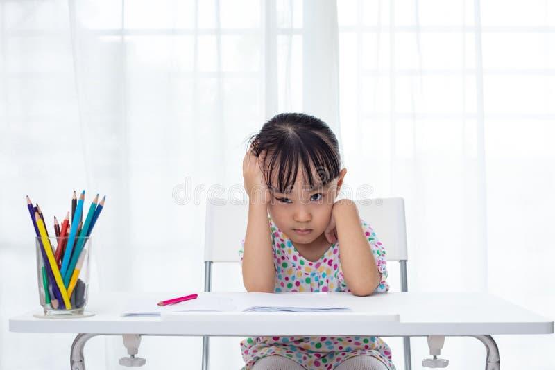 Menina chinesa pequena asiática que faz trabalhos de casa imagens de stock