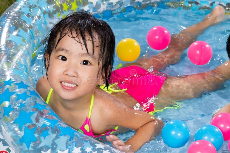 Menina chinesa pequena asiática que joga em um Swimmi de borracha inflável imagem de stock royalty free