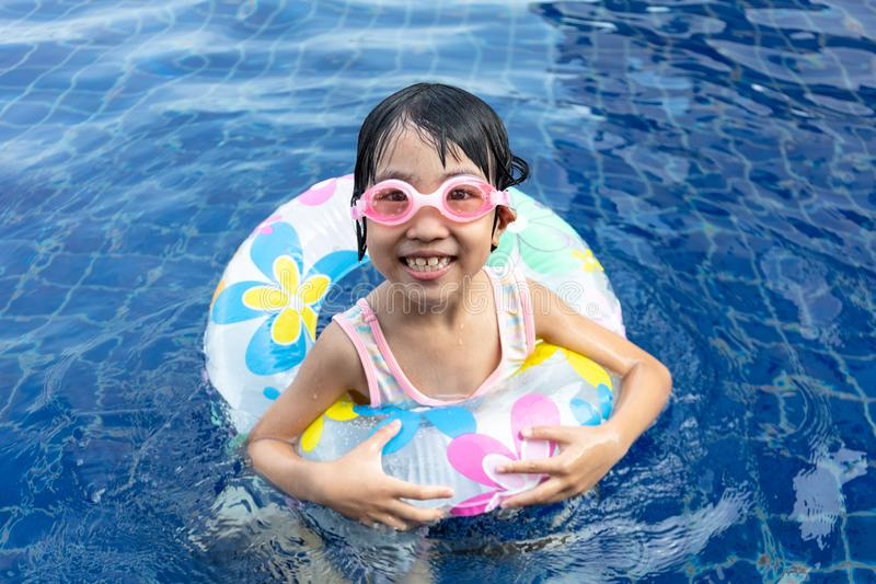 Menina chinesa pequena asiática que joga na piscina imagens de stock