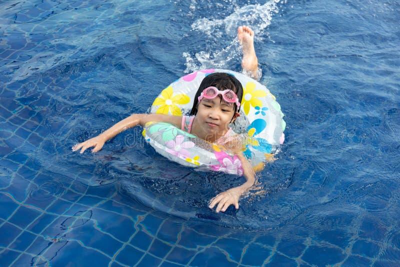 Menina chinesa pequena asiática que joga na piscina foto de stock