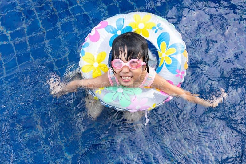 Menina chinesa pequena asiática que joga na piscina imagem de stock