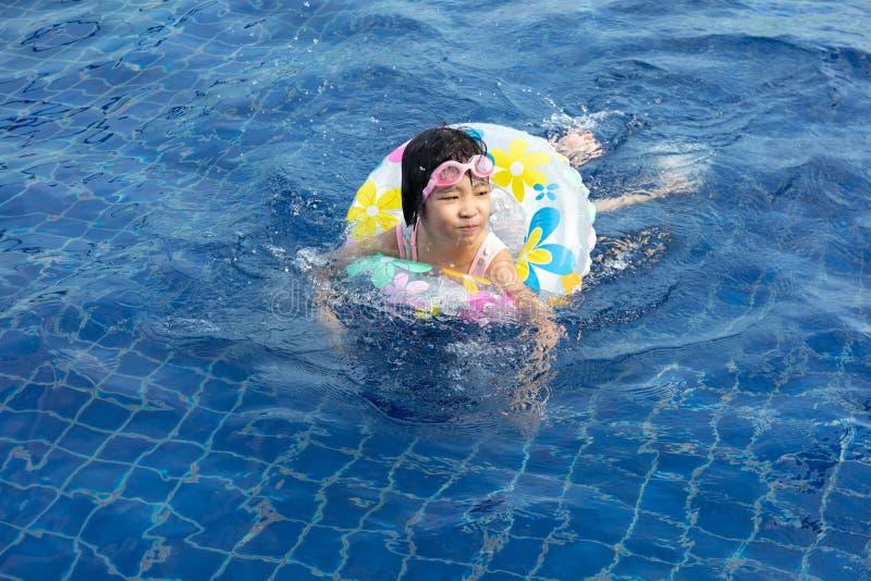 Menina chinesa pequena asiática que joga na piscina fotos de stock