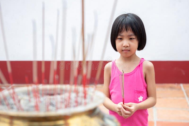 Menina chinesa pequena asiática que reza com as varas ardentes do incenso fotos de stock royalty free