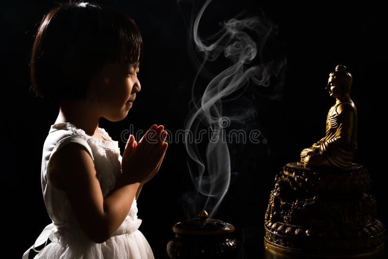 Menina chinesa pequena asiática que reza na frente da Buda imagens de stock