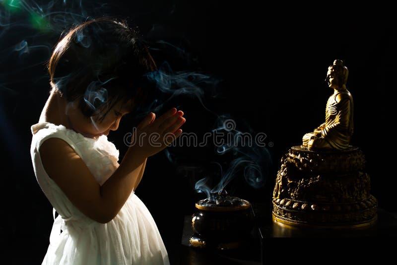 Menina chinesa pequena asiática que reza na frente da Buda imagens de stock royalty free