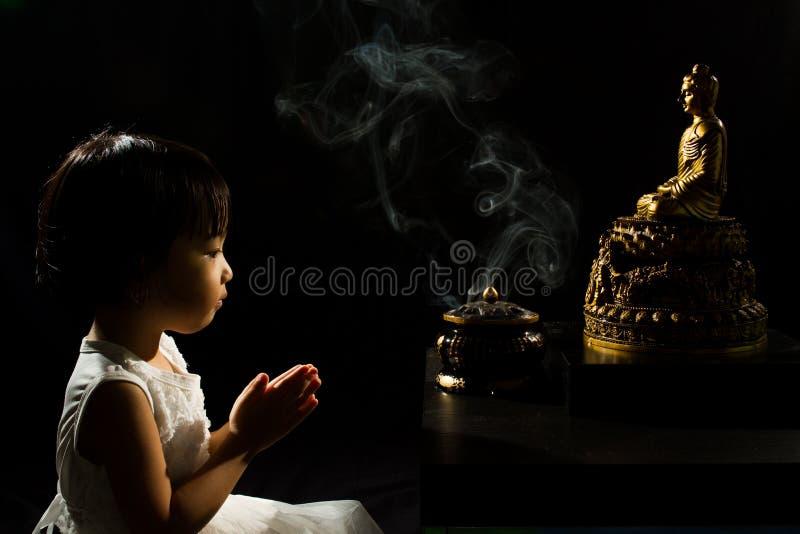 Menina chinesa pequena asiática que reza na frente da Buda fotos de stock