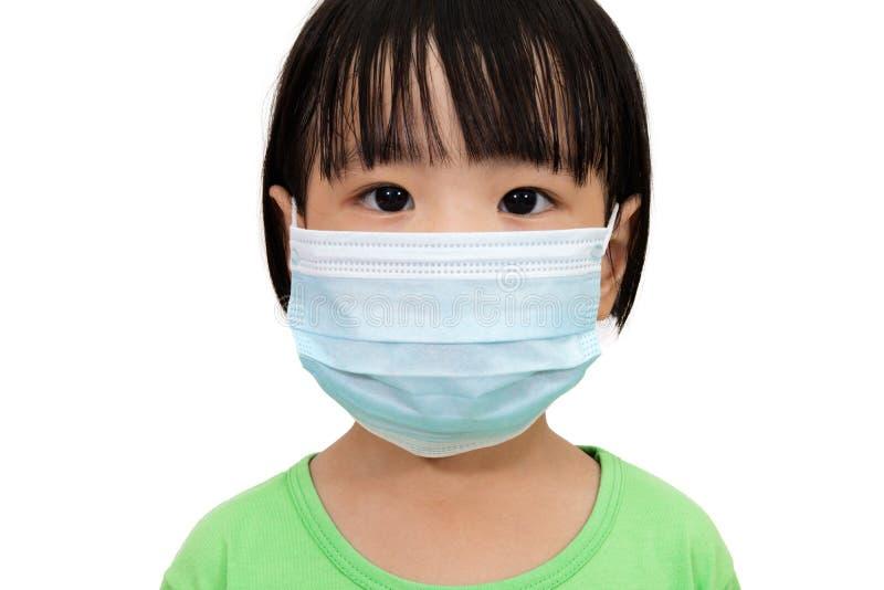 Menina chinesa pequena asiática que veste uma máscara protetora imagem de stock