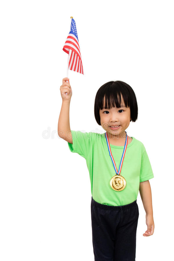 A menina chinesa pequena asiática sorri com uma medalha da bandeira e de ouro foto de stock royalty free