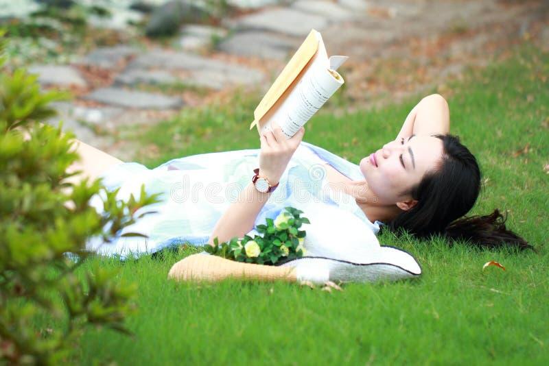 Menina chinesa que lê o livro Jovem mulher bonita loura com o livro que encontra-se na grama imagem de stock