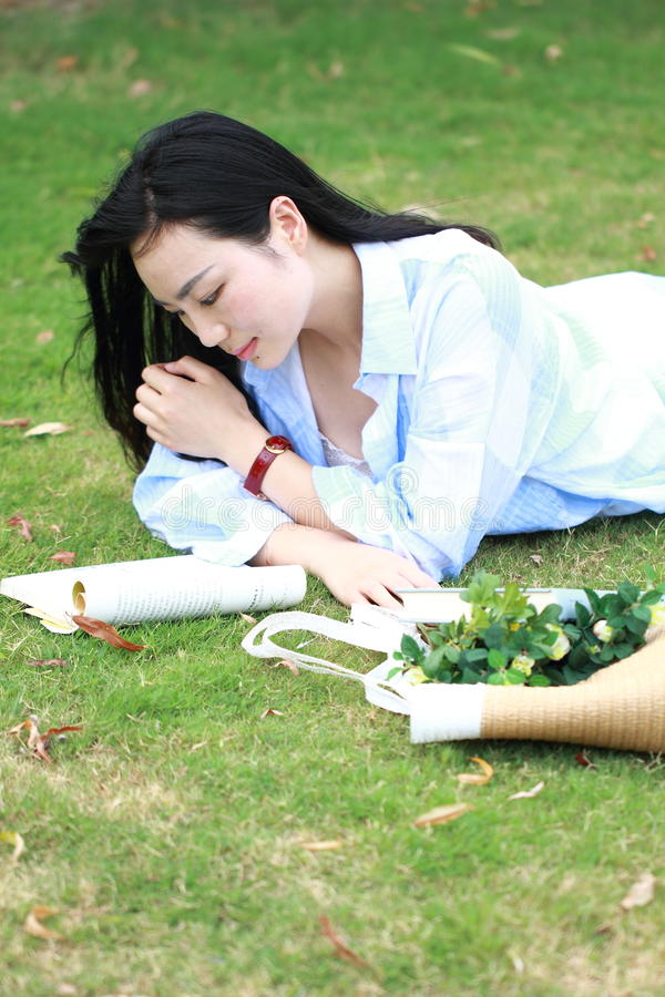 Menina chinesa que lê o livro Jovem mulher bonita loura com o livro que encontra-se na grama imagem de stock royalty free