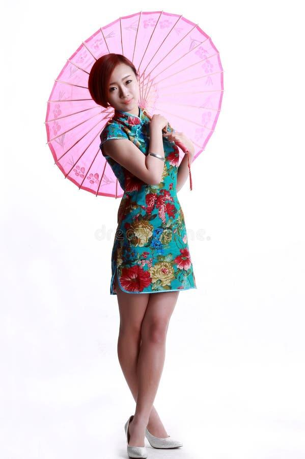 Menina chinesa que veste um guarda-chuva do cheongsam