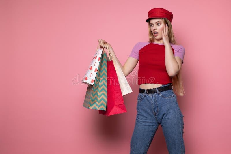 Menina chocada bonita nova no chap?u vermelho com sacos de compras coloridos foto de stock