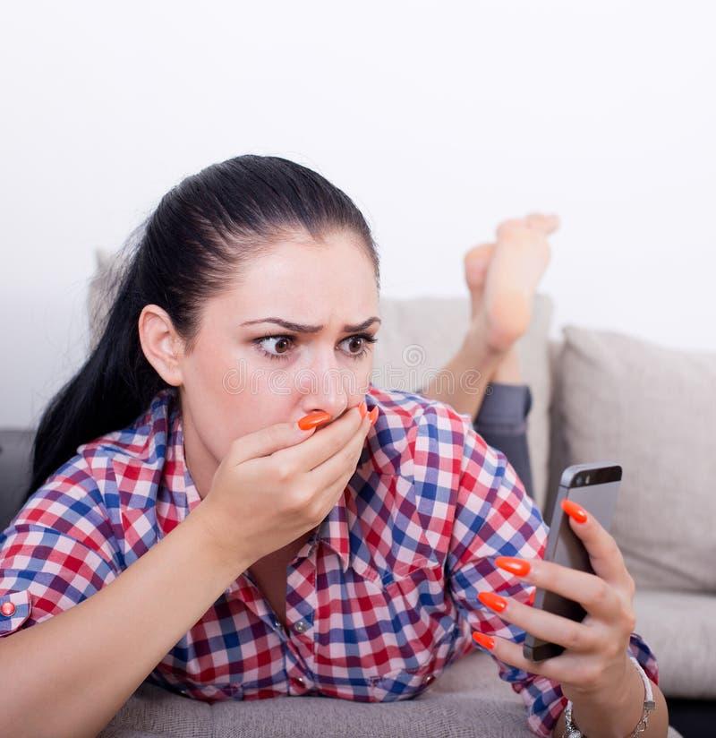 Menina chocada com o telefone celular no sofá imagem de stock